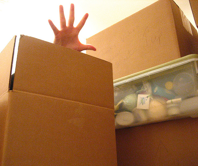 Picture of a hand reaching out of a full box
